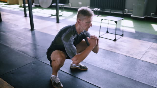 vídeos de stock e filmes b-roll de male fitness instructor showing squat exercise at modern plase. - agachar se
