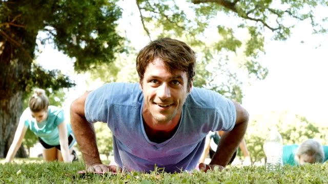 male fitness instructor smiles while doing push ups during outdoor exercise class - kurs ćwiczeń filmów i materiałów b-roll