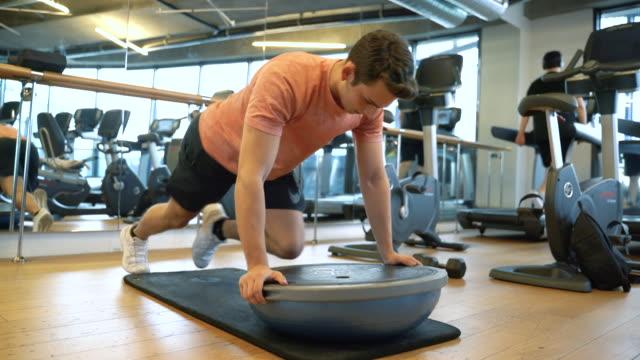 istruttore di fitness maschile che si allena con la palla di equilibrio bosu - metodo pilates video stock e b–roll
