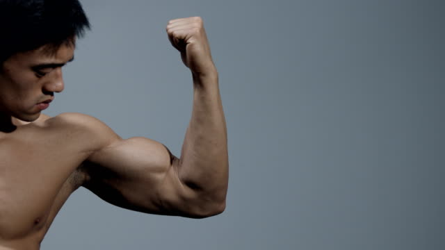 male fitness model stretches arm out his arm and flexes his bicep - napinać mięśnie filmów i materiałów b-roll