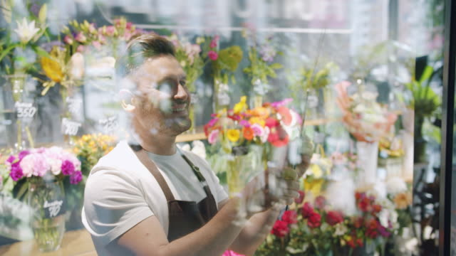 Male florist in apron changing closed sign to open on flower shop door smiling Male florist in apron is changing closed sign to we are open on flower shop door smiling welcoming customers. People, small business and start-up concept. opening event stock videos & royalty-free footage