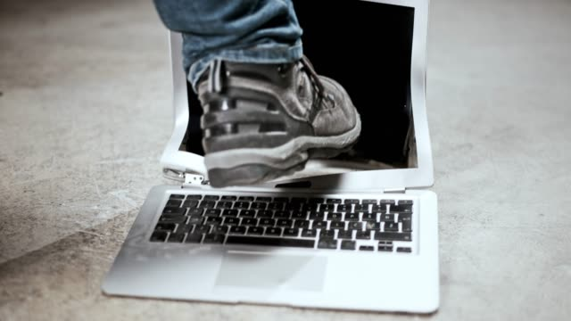 SLO MO Male foot kicking a laptop on the floor Slow motion wide locked down shot of a laptop being kicked by a man. Shot in Slovenia. demolishing stock videos & royalty-free footage