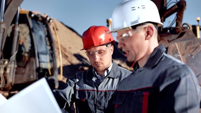manliga förman och arbetare i hjälm och glasögon diskuterar konstruktions plan tittar på ritning - excavator bildbanksvideor och videomaterial från bakom kulisserna