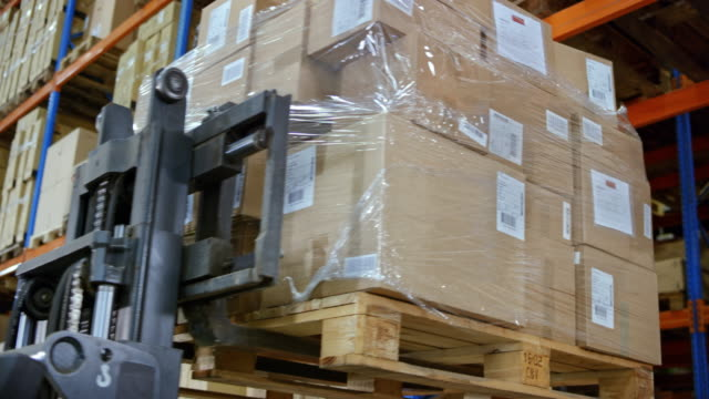 Male forklift operator bringing a pallet off the rack for the female supervisor to check the packages video