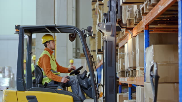 Male forklift operator taking a pallet off a rack in the warehouse