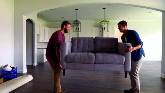 manliga vänner bära soffa i nya hem - flytta bildbanksvideor och videomaterial från bakom kulisserna