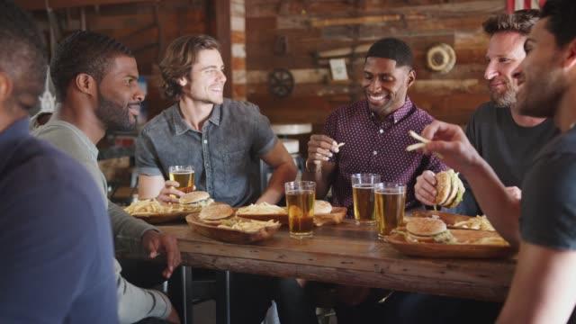 vídeos y material grabado en eventos de stock de hombres amigos bebiendo cerveza y comiendo hamburguesas en sports bar - hamburguesa