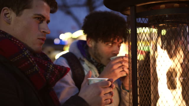 Male Friends Drinking Mulled Wine At Christmas Market video