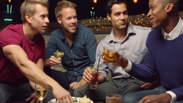 Male Friends Enjoying Night Out At Cocktail Bar Shot On R3D video