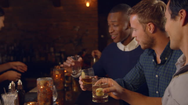 Male Friends Enjoying Night Out At Cocktail Bar, Slow Motion video