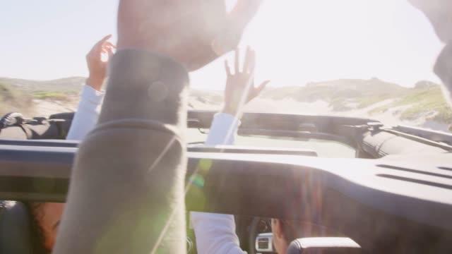 vidéos et rushes de amis de sexe masculin dans une voiture haut de la page ouverte avec les mains en l'air, rétro-éclairé - homme faire coucou voiture