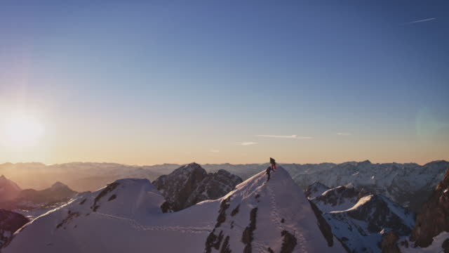 male friends reaching mountaintop during sunrise - in cima video stock e b–roll