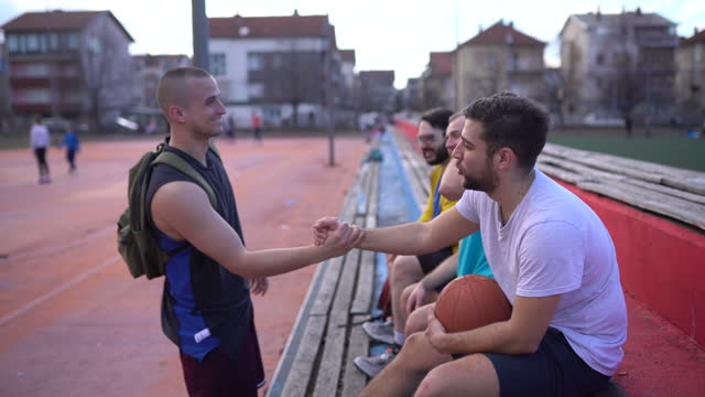 Male friends sitting on stands before playing basketball video