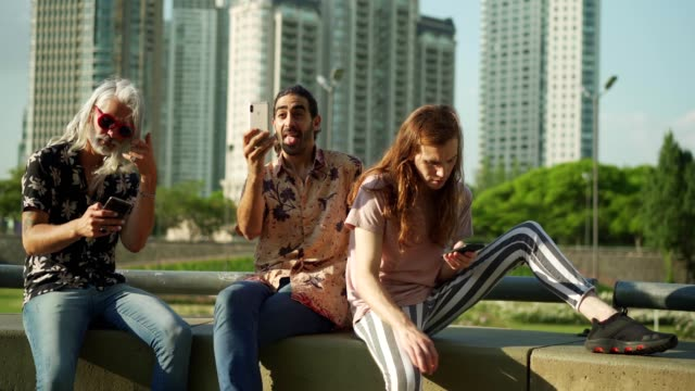Male friends using cellphones Male friends occupied with smart phones are sitting together outdoors. ignoring stock videos & royalty-free footage