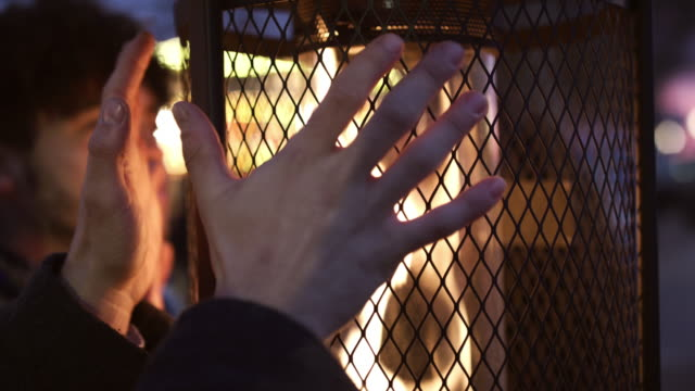 Male Friends Warming Hands On Outdoor Heaters At Night video