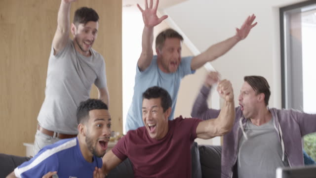 Male friends watching a match and celebrating Wide handheld shot of five male friends watching a match on TV and celebrating the score. Shot in Slovenia. match sport stock videos & royalty-free footage
