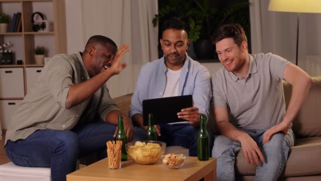 male friends with tablet pc drinking beer at home - happy hour video stock e b–roll