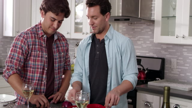 Male gay couple preparing a meal together, close up, shot on R3D video