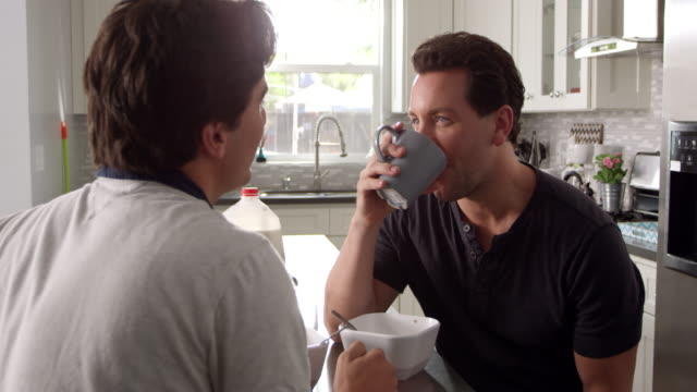 Male gay couple talking in their kitchen, close up, shot on R3D video