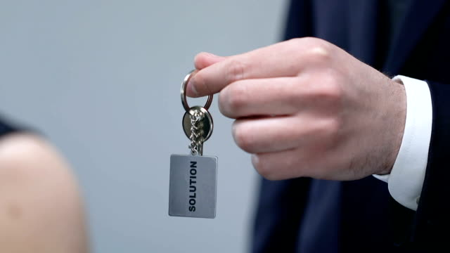 male giving woman keychain with solution word, helping with problem, support - key ring stock videos & royalty-free footage