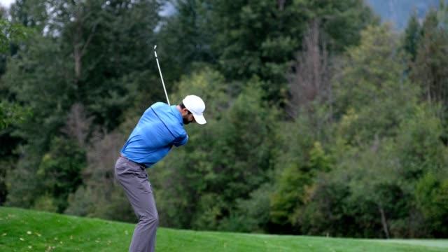 vidéos et rushes de le golfeur mâle frappe un grand projectile - golf