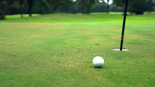 Male golfer is putting on green .