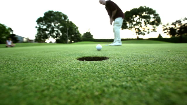 A male golfer sinks a put and gets excited. Wide shot. video