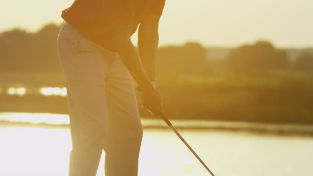 Male golfer teeing off on fairway at sunset video