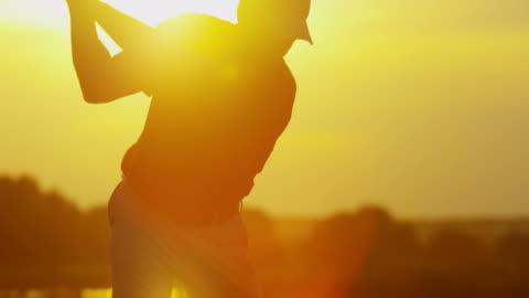 vidéos et rushes de golfeur masculin départs sur fairway au coucher du soleil - exactitude