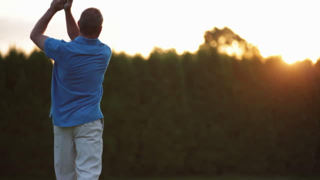 Male golfer tees off into the sunset. video