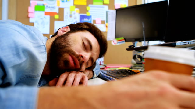 Male graphic designer sleeping at desk video