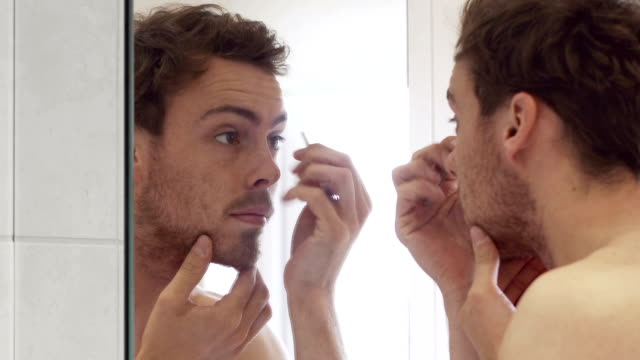 Male grooming    HE Close up video clip of a good looking (handsome) young man grooming himself in a bathroom mirror. He's trimming his beard & plucking facial hair. vanity stock videos & royalty-free footage