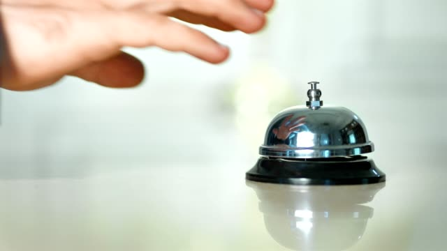 Male guest hand ringing on reception silver table bell at vintage hotel close-up