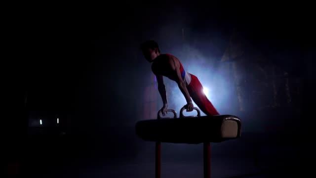 vídeos y material grabado en eventos de stock de atleta masculino de la gimnasta realiza handstand y un exprimido en caballo con arcos en un fondo oscuro y el humo en cámara lenta. programa olímpico. preparación para el ejercicio - gimnasia