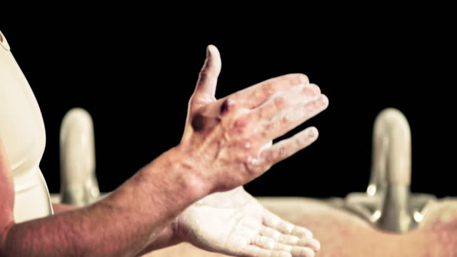 SLO MO Male gymnast clapping his chalky hands together video