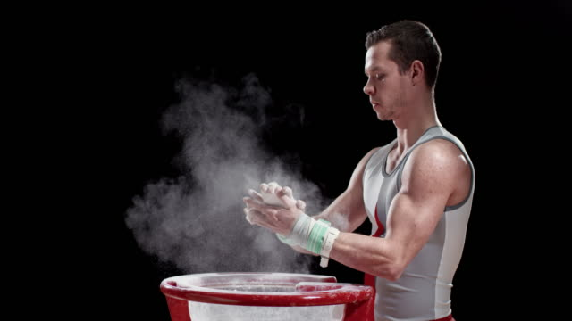 SLO MO Male gymnast clapping his wrapped hands over the chalk bowl video