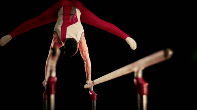 SLO MO Male gymnast doing a hand stand on parallel bars