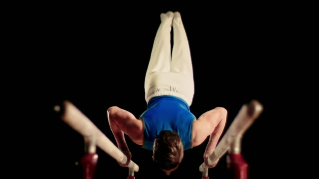 slo mo male gymnast doing his routine on parallel bars - gymnastics stock videos and b-roll footage