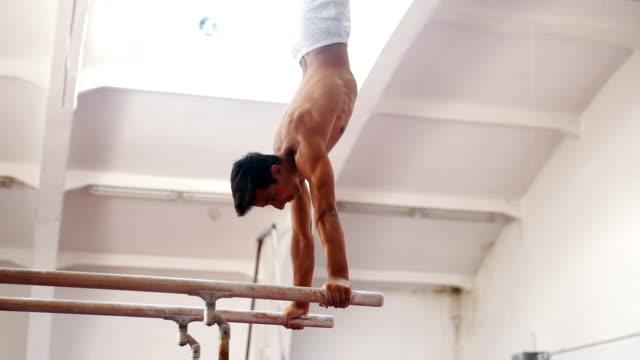 männlichen turner trainieren sie auf parallel bar - turngerät mit holm stock-videos und b-roll-filmmaterial