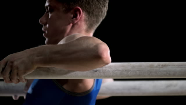 SLO MO Male gymnast on parallel bars performing his routine