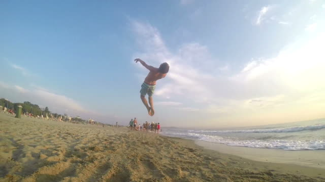 Male gymnast performing freerunning style backflip on beach. Steadycam SLOW MOTION video