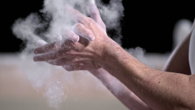 SLO MO Male gymnast removing excess chalk by clapping hands video