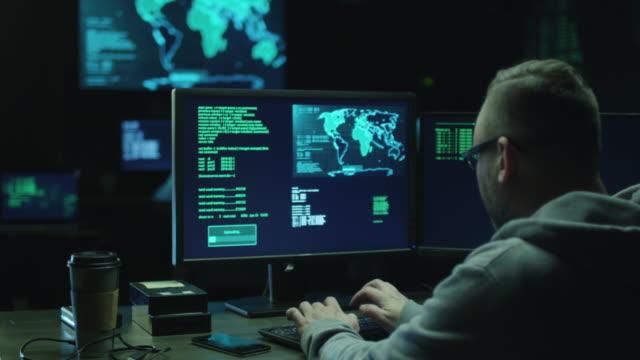 Masculino hacker no capuz funciona em um computador com mapas e exibição de dados em telas em um quarto escuro de escritório. - vídeo