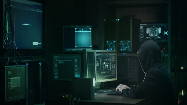 male hacker in a hood works on a computer with maps and data on display screens in a dark office room. - nazionalità russa video stock e b–roll