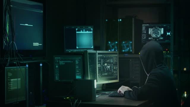 Männliche Hacker in eine Kapuze, die arbeitet auf einem Computer mit Karten und Informationen über die Bildschirme in einer dunklen Büro Zimmer. – Video