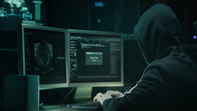 male hacker in a hood works on a computer with maps and data on display screens in a dark office room. - anonymous hackers stock videos and b-roll footage
