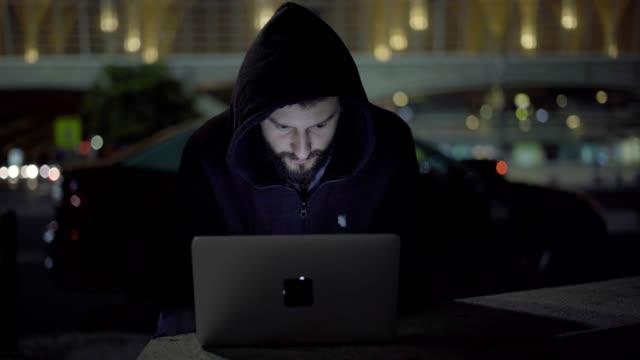vídeos de stock e filmes b-roll de male hacker in hood teleworking on laptop on street in night city - capuz