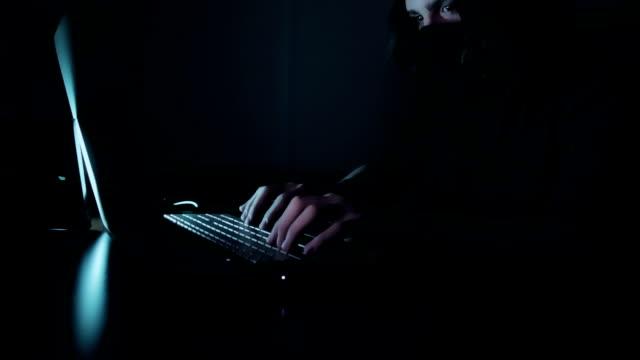 Erkek hacker bir karanlık office odada bir bilgisayarda çalışıyor. video