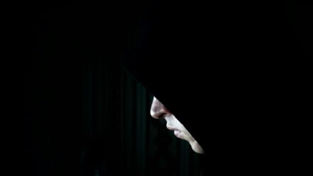 vídeos de stock e filmes b-roll de male hacker working on a computer in a dark office room - capuz