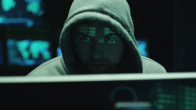 Male hacker working on a computer while green code characters reflect on his face in a dark office room. Male hacker working on a computer while green code characters reflect on his face in a dark office room. Shot on RED Cinema Camera in 4K (UHD). cyborg stock videos & royalty-free footage